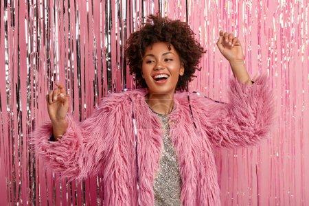 Photo pour Joyful black woman dances actively, makes movements, raises hands, wears fur coat, smiles broadly, enjoys favorite music, has fun on shindig - image libre de droit