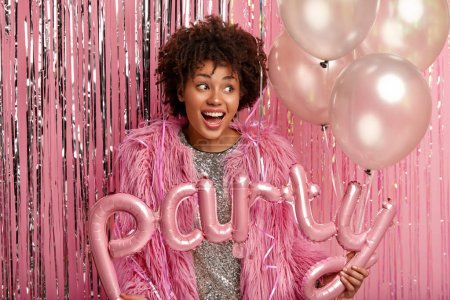 Photo pour Good humored lovely dark skinned female has curly hair, focused aside dressed in long fur coat, holds air balloons glad to organize unforgettable party with peers stands over decorated pink background - image libre de droit