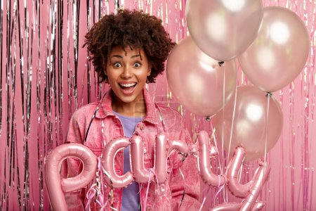Photo pour Magnificent curly Afro young woman with happy smile, has good time during party, wears stylish jacket, holds bunch of balloons and letter shaped word, isolated over pink background. Monochrome - image libre de droit