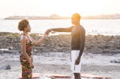 black race african american  couple ready to dance together at the beach during a sunset. golden tones and colors and vacation scenic background for beautiful man and woman blacks