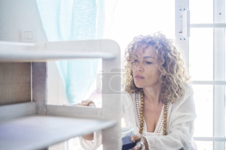 beautiful caucasian woman diy do it herself yourself a furniture renewed at home with the window light. concentrated expression for middle age lady painting with white paint