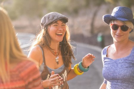 Groupe de trois belles filles jeune caucasien s'amuser en toute amitié tous ensemble en plein air avec image de coucher de soleil arrière légère et dorée des tons chauds. rire et joie. Mode robes avec des bracelets et des colliers