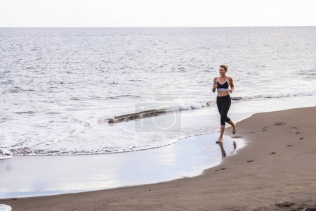 lonely girl blonde runner on the shore at the beach. morning activity to stay healthy and nice with your body. barefoot run at the beach, jogging and footing activity outdoor concept