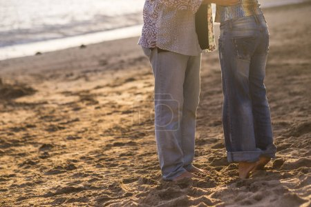 Couple in love having romantic tender moments at sunset on the beach - Young lovers having tender moments in summer vacation - Love concept - Soft focus on them - Matte filter with soft golden light