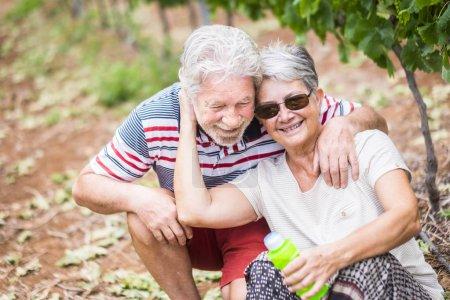 Photo pour Beau couple d'âge mûr caucasien vivent ensemble pour toujours et jouent avec du savon à bulles comme les enfants dans la campagne. activités de loisirs en plein air sans stress pour les retraités - image libre de droit