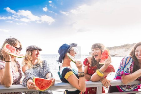 group of females friends stay together and have fun in the summer eating a watermelon. smiles and laugh enjoying a perfect sunny day of vacation