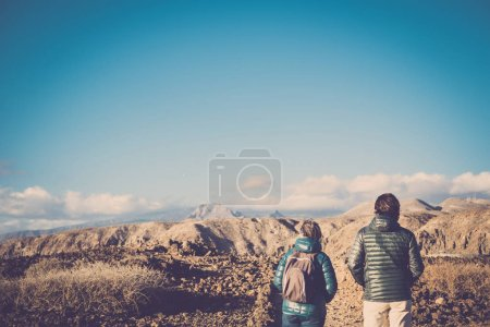 Senior mother and 45 year old son spend time together walking on an isolated path doing some trekking activity on mountains during the summer in a sunny day. vintage filter colors. looking the panorama