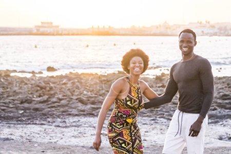 Foto de Par de piel de la raza africana negra feliz juntos divirtiéndose en la playa en vacaciones. concepto de la felicidad con dos jóvenes hombre y mujer que se divierten juntos. centrarse en el hombre - Imagen libre de derechos