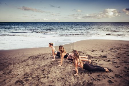 Three Caucasian young ladies doing Pilates on the shore near the  waves and the ocean. outdoor leisure activity sport and lifestyle fitness for beautiful women. freedom and healthy. great landscape.