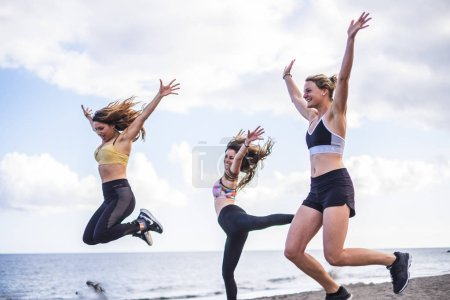 three beautiful  Caucasian girls jumping on the beach doing fitness workout. outdoor leisure sport activity for group of females people with ocean in background