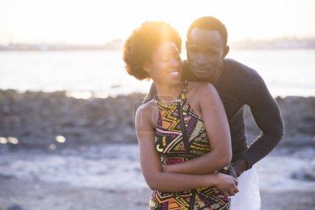 Foto de Hermosa pareja de modelos africanos de raza negra en vestido tradicional diversión y amor juntos en la playa en verano, durante la puesta de sol. bonito contraluz del sol, concepto de relación exterior - Imagen libre de derechos