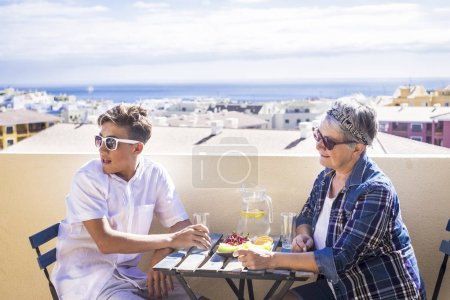 couple young and old people woman and boy grandmother and nephew for family concept lifestyle leisure activity eating something on the terrace rooftop with amazing ocean and buildings view in vacation