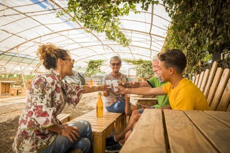 family drinking and cheers together in outdoor leisure activity in a restaurant made by recycled wood and in respect with the nature. everybody smile and enjoy the easy lifestyle. from young to old ages
