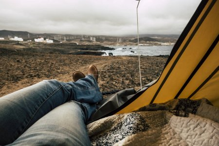 relaxed lady in a legs point of view inside a tent on the roof top of the car. travel and adventure concept with a tiny house with nature outdoor ocean view. spirit of adventure and discover beautiful places