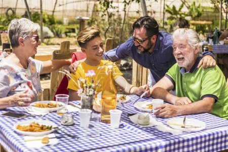 family caucasian people having lunch in natural alternative restaurant all together with joy and fun. smiling and laughing three different generations have nice leisure activity in a sunny day of vacation
