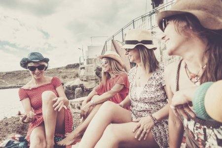 nice group of beautiful women young friends stay outdoor celebrating and enjoying friendship and relationship in vacation activity. colors and happiness with white houses sea style background