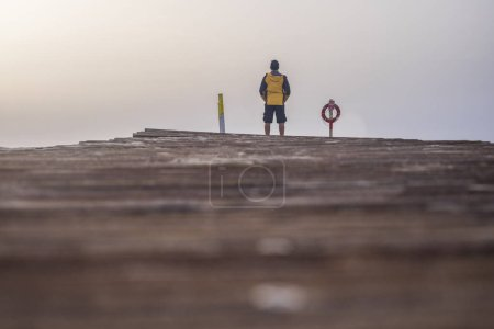 man standing at end of wooden path and looking at sea