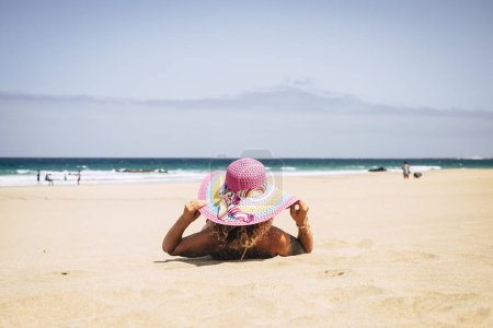 woman in colorful hat relaxing on beach during holidays