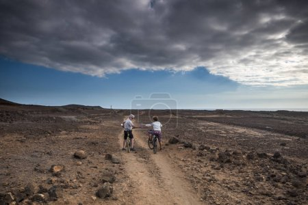 aged couple of mountain riders on ground road, leisure activity outdoor