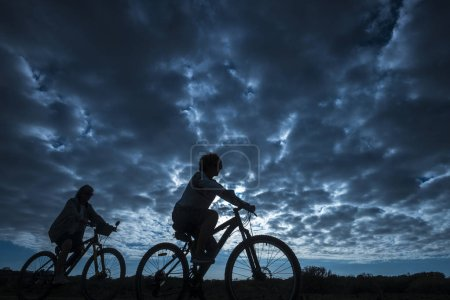 aged couple of mountain riders on cloudy sky background, leisure activity outdoor