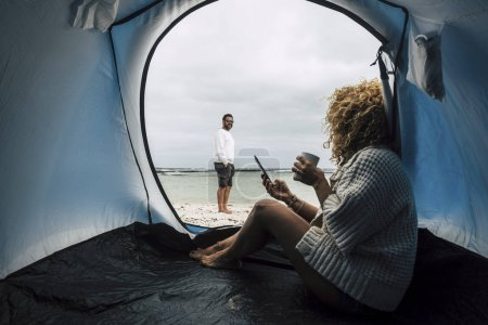 couple of Caucasian travelers camping on beach near ocean