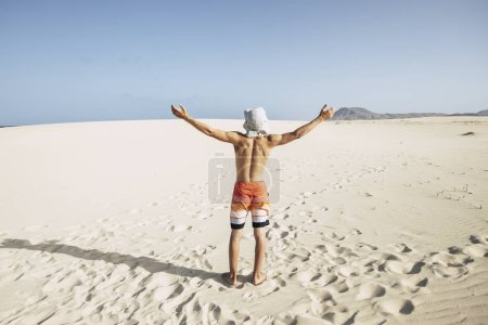 Photo for Teenager standing with open arms at beach and enjoying freedom - Royalty Free Image