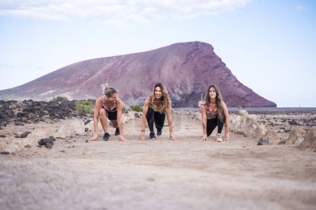 Photo for Three young runner girls ready to start and run for hard workout and fitness - Royalty Free Image