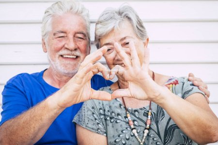 Happy senior couple hugging and making heart sign by fingers at summer day