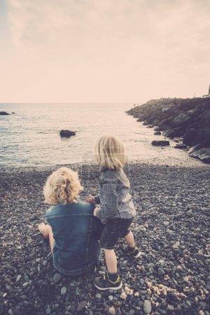 Photo pour Heureux couple famille fils mère assis à la plage s'adonner à des activités de loisirs en plein air regarder la mer tranquille dans l'amour et la tendresse pour toujours - image libre de droit