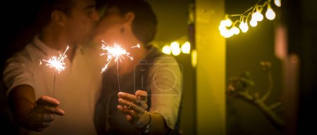 couple kissing during party at home, celebrating with sparkles light