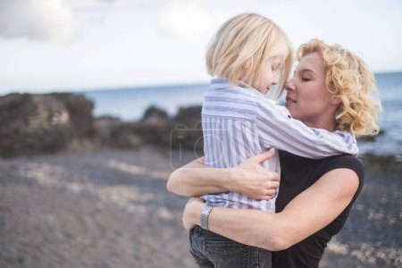 Photo pour Young beautiful blonde salope mother woman kiss her son fils while hug him with love and togetherness emotion and feeling - image libre de droit