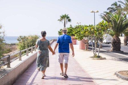 Senior couple on holidays walking near sea at summer season