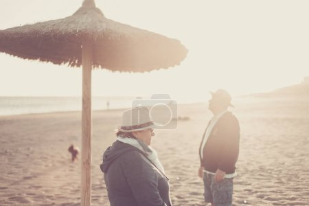 Photo for Senior aged couple at the beach in winter during sunset and sun in backlight - Royalty Free Image