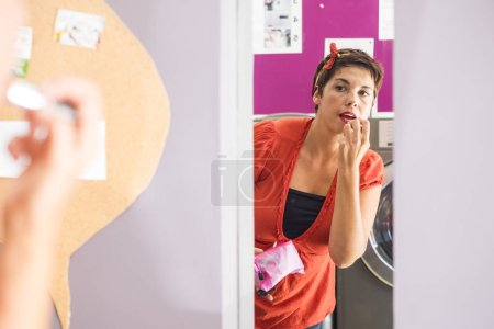 Photo for Young brunette lady doing lipstick make up in laundry mat store in the town - Royalty Free Image
