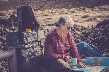 Photo for Aged beautiful woman sit down in the outdoor during trekking travel with backpack and paper map enjoying nature and alternative vacation lifestyle with freedom and feeling with the world path - Royalty Free Image