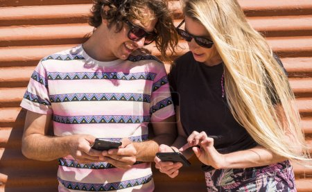 Photo for Millennial young people couple together using both cellular mobile phone looking the devices - Royalty Free Image