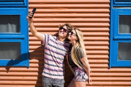 Photo for Young beautiful millennial couple of people man and woman taking selfie picture together in relationship for summer holiday - Royalty Free Image