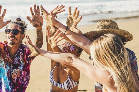 Photo pour Amis les gens en vacances d'été à la plage montrent leurs mains ensemble saleté de sable après une drôle de journée d'activité à la mer style de vie - image libre de droit