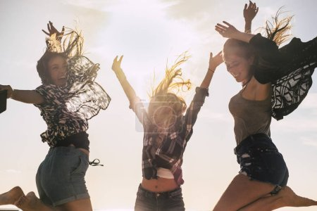 Photo for Happy young people concept youthful girls jumping and laughing together in friendship - Royalty Free Image