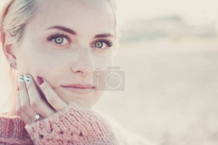 Photo for Defocused portrait with focus on clear eye of a beautiful girl model young sit down and looking to you on camera. little smile relaxed for lifestyle concept - Royalty Free Image