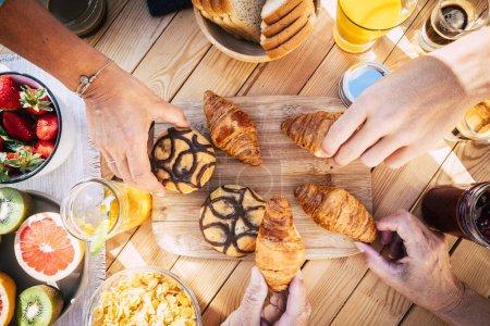 Photo pour Vue verticale de la table en bois et les gens ensemble pour le petit déjeuner en amitié - image libre de droit