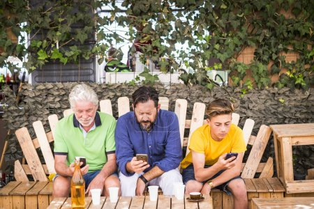 Photo for Family generations men with grandfather father and son nephew from old to young stay together using cellular technology smartphone to connect to internet and check modern related concepts - Royalty Free Image