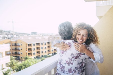 Photo for Love for friends or family concept with curly beautiful happy middle age woman hugging a mature grey hair senior lady on the terrace at home with city view down - Royalty Free Image