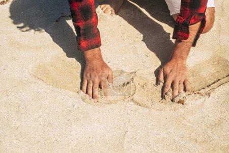 Photo pour Plage de sable et les mains masculines touchant et se déplaçant profiter de l'été - image libre de droit