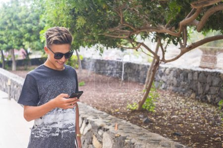 Photo for Handsome young people caucasian boy use cellular mobile phone outdoor - Royalty Free Image