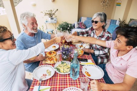 Photo for Group of mixed generations people have fun together during lunch at home in outdoor terrace - Royalty Free Image