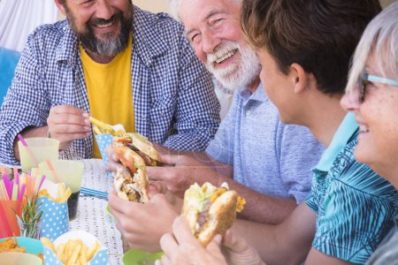 Photo for Group of friends or family eating together lunch with hamburger and fried potatoes together - Royalty Free Image