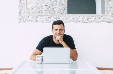 Photo pour Happy millennial business young man sit on his desk with modern technology computer laptop smiling at the camera - image libre de droit