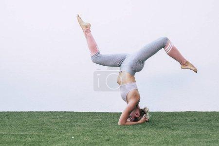 Photo pour Yoga acrobatique sport de plein air loisir et bien-être concept de fitness avec jeune athlète femme en position inverse - image libre de droit
