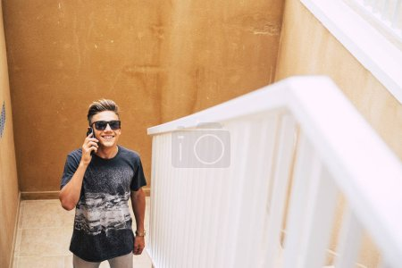 Photo for Attractive teenager waiting at someone on the stairs while his calling and talking with someone with his phone - Royalty Free Image